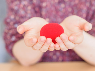 Red gift box hold in woman hands like heart shape. Concept of the engagement gift. Valentine surprise gift, symbol of love.