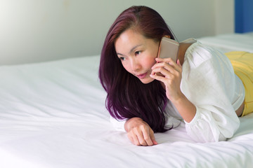 Sexy Woman using a smart phone on bed.