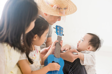 Asian family playing ukulele and harmonica at home