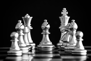 The King in battle chess game stand on chessboard with black isolated background. Business leader concept for market target strategy. Intelligence challenge and business competition success play..