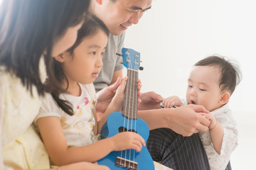 Family playing ukulele at home