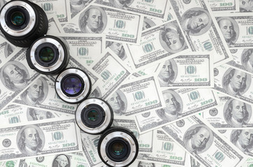 A few photographic lenses lies on the background of a lot of dollar bills. Space for text