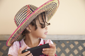 Child with hat playing with phone