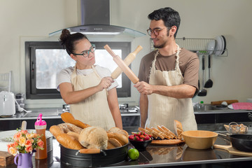 Happy Couple Cooking Together with Bread and strawberry jam in kitchen
