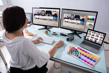 Female Designer Working On Multiple Computer Wall mural