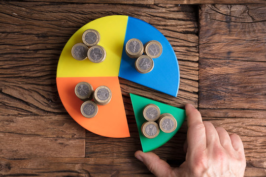 Businessperson Taking Piece With Money From Pie Chart