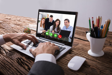 Businessperson Video Conferencing With Colleague On Laptop