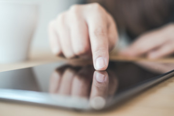 Closeup image of a woman's hand pointing , touching and using tablet pc