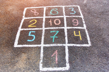 Closeup of hopscotch drawn with chalk on asphalt road. Children games and outdoor activities.