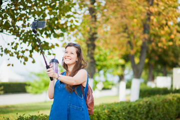 Young woman with smoothie selfie stick photo herself outdoors. trendy girl have fun with her smartphone shooting for video blog or social net