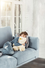 Sweet dreams. Adorable little fair-haired boy hugging his favourite nice toy and lying on the sofa while taking a nap