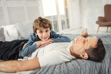 My best father. Nice delighted fair-haired boy smiling and his daddy while lying on his back on the sofa and they relaxing together