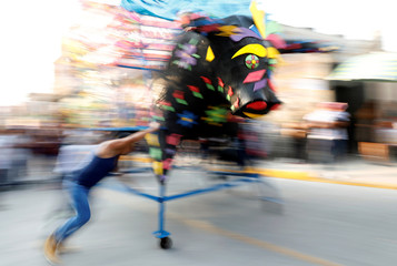 """Man spins a traditional bull figure surrounded by fireworks, known as """"El Torito"""", during the annual San Juan de Dios celebrations in Tultepec"""