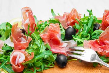 chopping board with aragula and raw ham