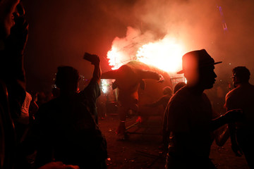 """People enjoy fireworks exploding from a traditional bull figure known as """"El Torito"""" in Tultepec"""