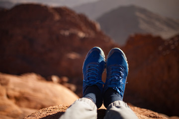 Male legs in sneakers over cliff against backdrop of mountain.