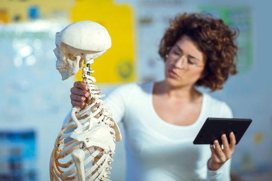 Medical doctor woman teaching anatomy using human skeleton model