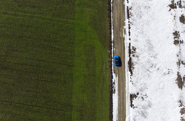 aerial view of green spring field and snow from the drone. car in the road scene