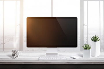 Wall Mural - Computer display with blank screen for mockup in office or work room. Window and sun light in background. Cup of coffee and two plants beside.