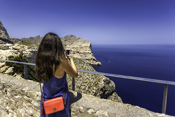 Back view of young woman in a blue dress photographing a view of sea and mountain with her phone