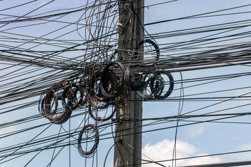 Messy wires attached to the electric mast. The chaos of cables and wires on an electric pole. Many electrical cable - wire and telephone line on electricity post, Thailand.