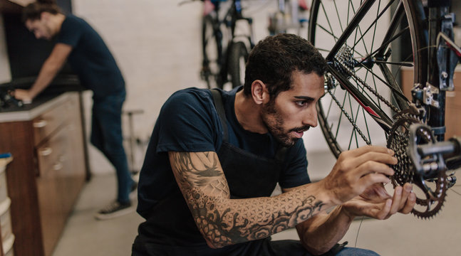 Mechanic repairing a bicycle in workshop