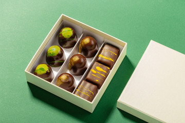 Assortment of luxury bonbons in box on green background