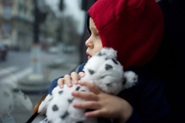 Child Travelling on Bus - holding soft toy