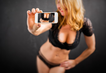Woman in lingerie taking sexy selfie photo with mobile phone