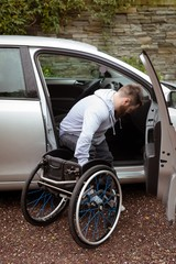 Disabled man on wheelchair boarding in his car