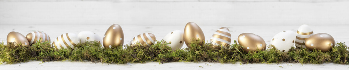 easter decoration, gold painted eggs on moss against a gray white wooden background, extra wide panoramic banner, copy space