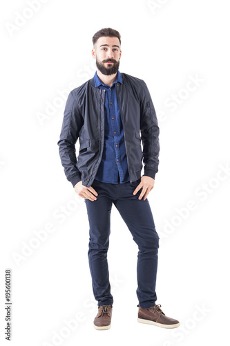 2534e0e3c20a Young man in blue shirt and bomber jacket with thumbs in pockets looking at  camera. Full body isolated on white background.