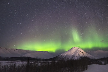 Night Starry Sky and Green Northern Lights in Snowy Mountains at Winter Night