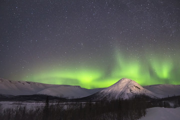 Night Starry Sky and Green Northern Lights. Snow-Capped Mountains at Winter Night