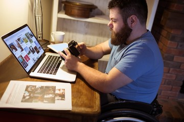 Disabled man looking at photos in camera