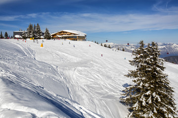 Panoramic view of ski slope in winter sunny day at the mountain ski resort of Alpbachtal, Wildschönau, Austria. People skiing down the hill.