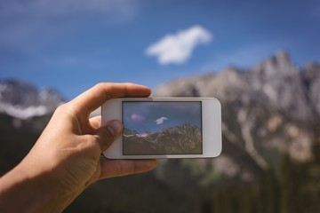 Man taking photo of mountains with mobile phone