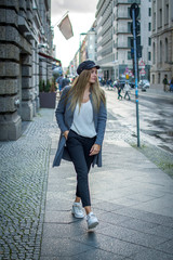 Stylish young woman walking through the streets of Berlin.