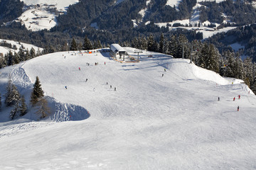 People skiing down the slope. Ski slope in winter sunny day at the mountain ski resort of Alpbachtal, Wildschönau, Austria