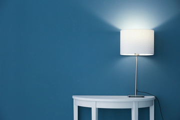 Elegant lamp on table near color wall