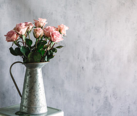 Dozen Pink Roses in Silver base in front of textured wall