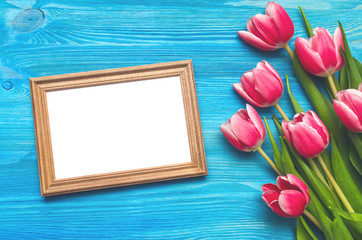 Tulip flowers and empty photo frame of a loved one copy space on blue wooden table board background. Woman day concept. Mother day background. Saint Valentines day greeting card . Romantic background.