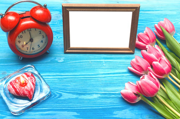 Tulip flowers and empty photo frame of a loved one copy space, alarm clock and burning candle on blue wooden table board background. Woman day concept. Mother day background. Saint Valentines day.