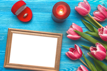 Tulip flowers wedding ring in a gift present box and empty photo frame of a loved one copy space on blue wooden table board background. Marriage offer.  Woman day concept. Saint Valentines day.