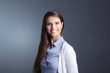 Portrait of a businesswoman , against dark background. Woman smiling. Portrait of a woman