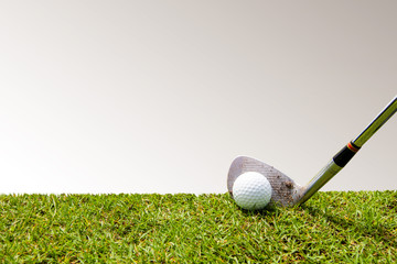 Golf club and golf ball in grass with copy space on gray background.