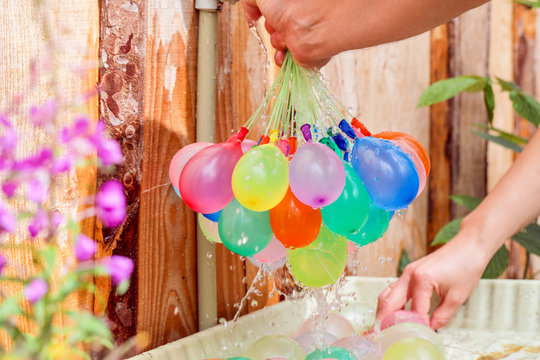 Filling colorful  water balloons with water