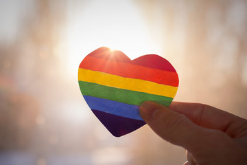 lgbt rights concept,  hand holds a heart painted like a LGBT flag, silhouetted against sun