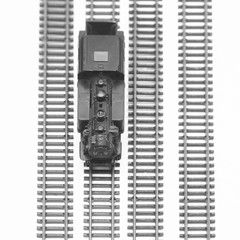 Vintage black model railway isolated on white background. View from above. Focused to front of locomotive. Selective focus.