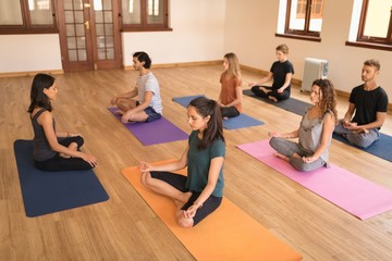 Group of people meditating in fitness club